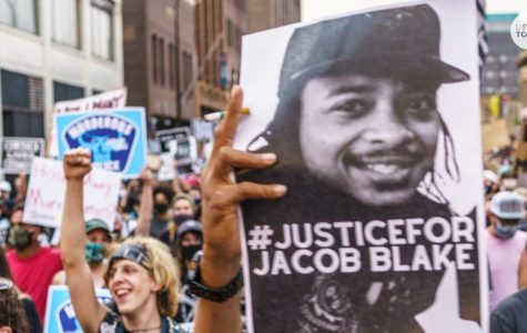 Protests holding sign with picture of Jacob Blake